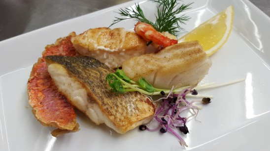 Gebratene Mittelmeerfische (Tagesempfehlung) mit roter Pfeffer-Knoblauch-Sauce, Weißbrot und Salaten