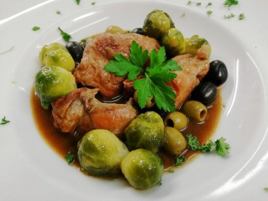 Geschmorte Kaninchenkeule mit Oliven in Kräutersoße, Rosenkohl, Kartoffeln und Salaten